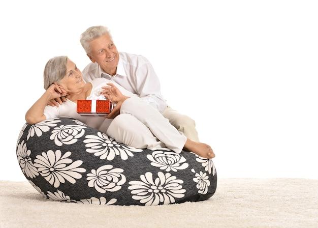 Casal sênior sentado em uma poltrona e comemorando o feriado com um presente