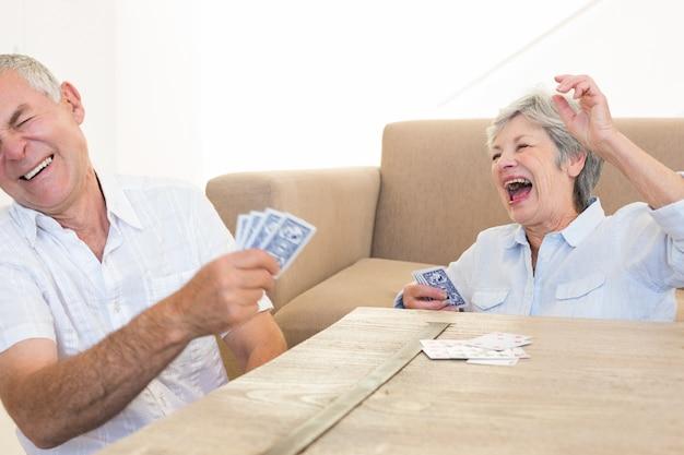 Casal sênior sentado no chão jogando cartas