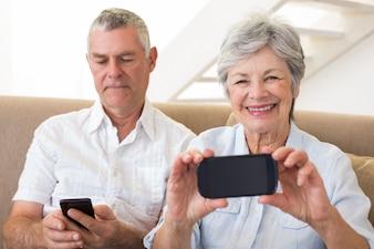 Casal senior sentado no sofá usando seus smartphones