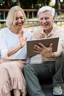 Casal sênior sorridente acenando para um tablet ao ar livre