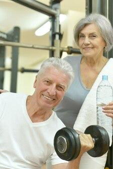 Casal sênior sorridente bebendo água após se exercitar na academia
