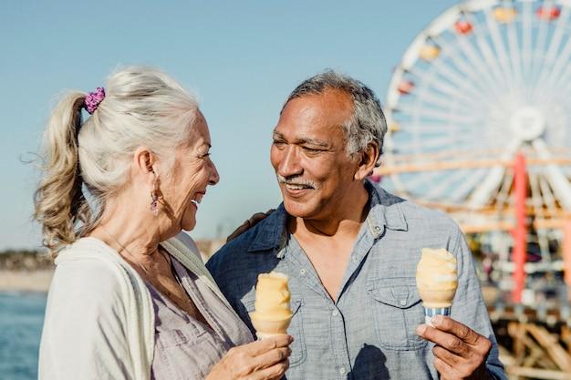 Casal sênior sorridente tomando sorvete no píer de santa monica