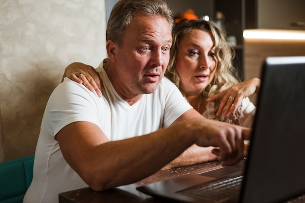 Casal sênior surpreso olhando para laptop