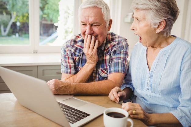 Casal sênior surpreso usando laptop em casa