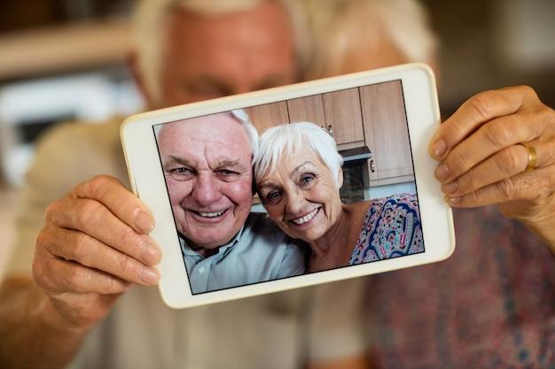 Casal sênior tirando selfie com tablet digital na cozinha de casa
