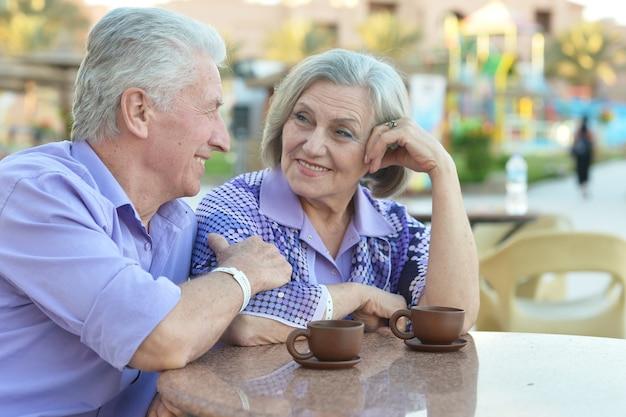 Casal sênior tomando café no resort durante as férias