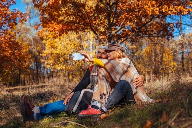 Casal sênior tomando selfie no parque outono. homem e mulher felizes curtindo a natureza e abraçando