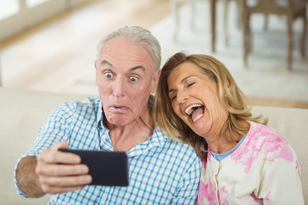Casal sênior tomando uma selfie no celular na sala de estar