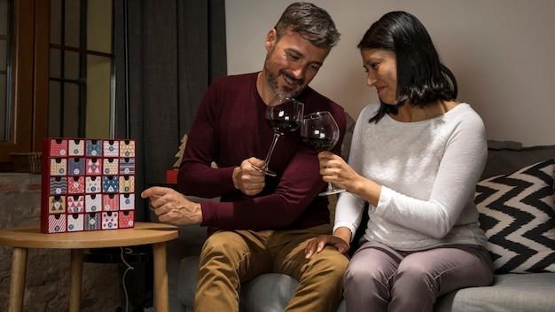 Casal sênior torcendo com taças de vinho