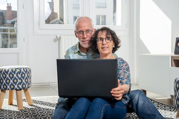 Casal sênior usando computador laptop em casa para compras on-line