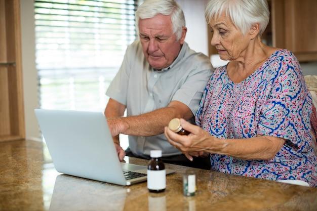 Casal sênior usando laptop e segurando o frasco de comprimidos na cozinha de casa