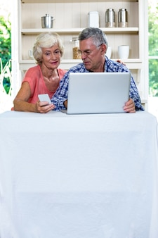 Casal sênior usando laptop e telefone celular em casa