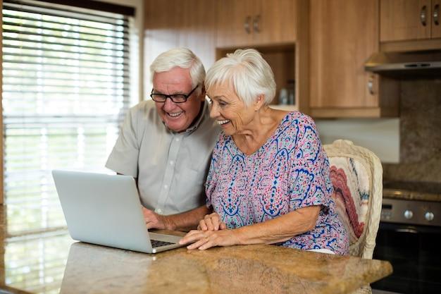 Casal sênior usando laptop na cozinha de casa