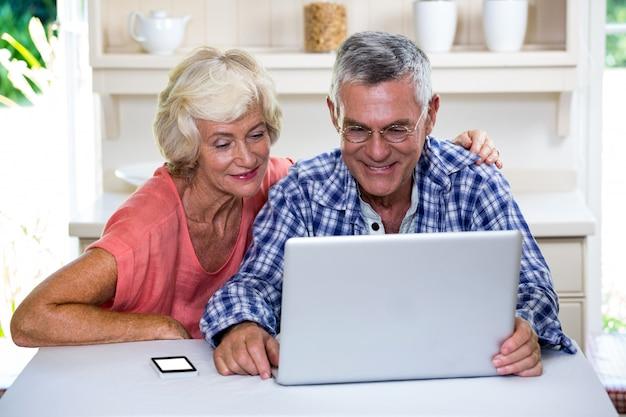 Casal sênior usando o laptop em casa