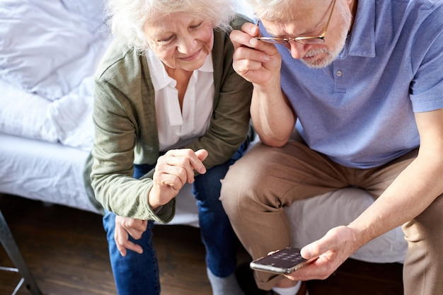 Casal sênior vai fazer videochamada no telefone com a família, conversa online. distância social, família em casa, tecnologias modernas