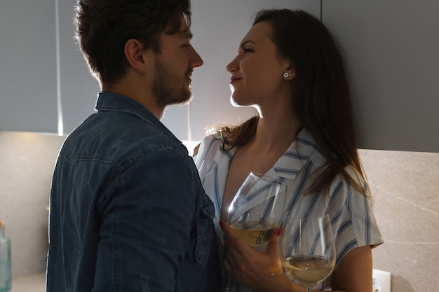 Casal sensual bebendo vinho e relaxando em casa