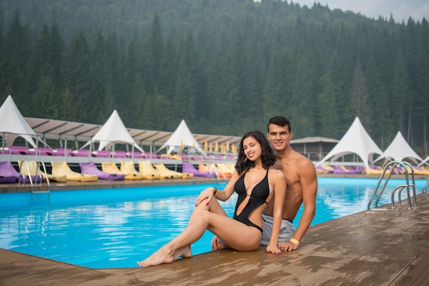 Casal sentado à beira da piscina no luxuoso resort