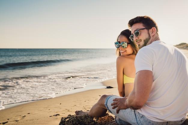 Casal sentado à beira-mar