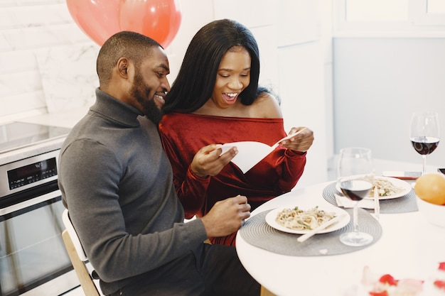 Casal sentado à mesa, comendo, conversando e rindo no dia dos namorados