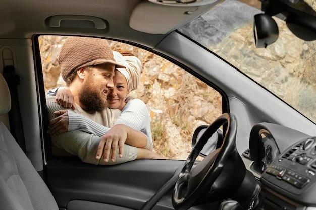 Casal sentado ao lado do carro