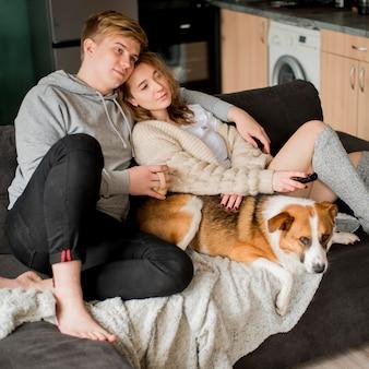 Casal sentado com cachorro no sofá