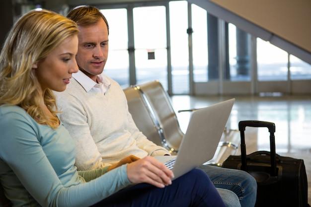 Casal sentado com laptop na sala de espera