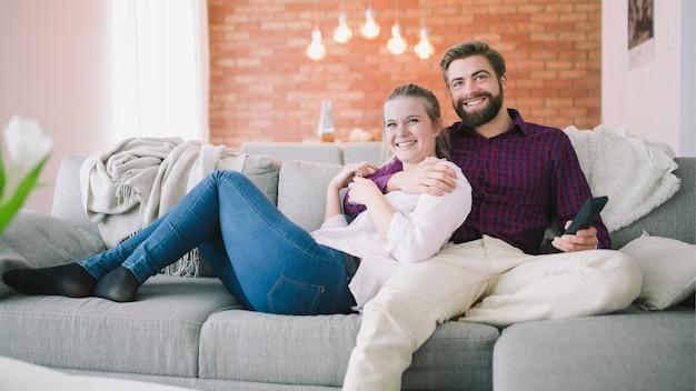 Casal sentado e assistindo televisão juntos