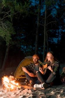 Casal sentado e cantando por uma tenda à noite
