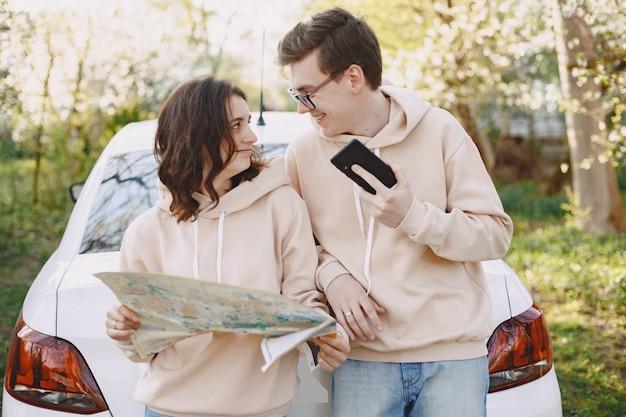 Casal sentado em um capô de carro em um parque