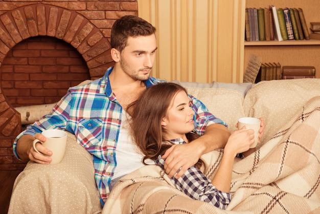 Casal sentado em um sofá tomando café