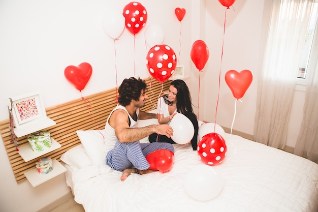 Casal sentado em uma cama com os balões em todos os lugares