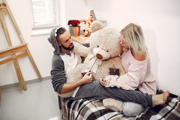 Casal sentado em uma cama em um quarto, bebendo café
