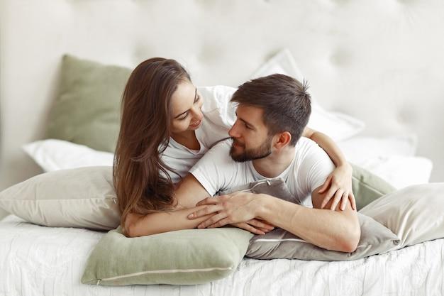 Casal sentado em uma cama em um quarto Foto gratuita