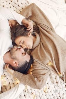Casal sentado em uma cama em um quarto