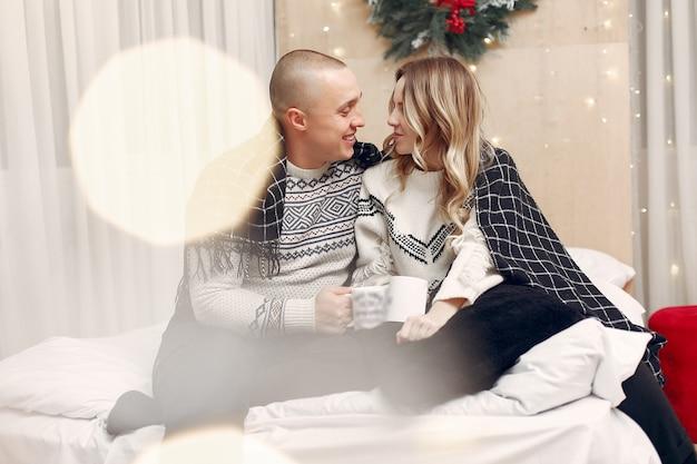 Casal sentado em uma cama tomando café