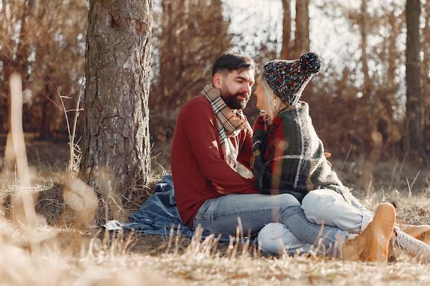 Casal sentado junto a uma árvore em uma floresta de primavera