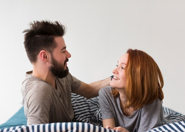 Casal sentado na cama e olhando um ao outro