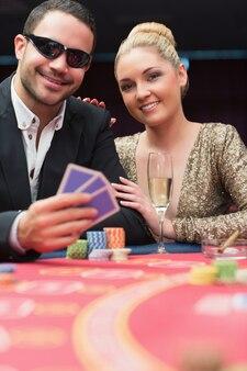 Casal sentado na mesa de poker sorrindo