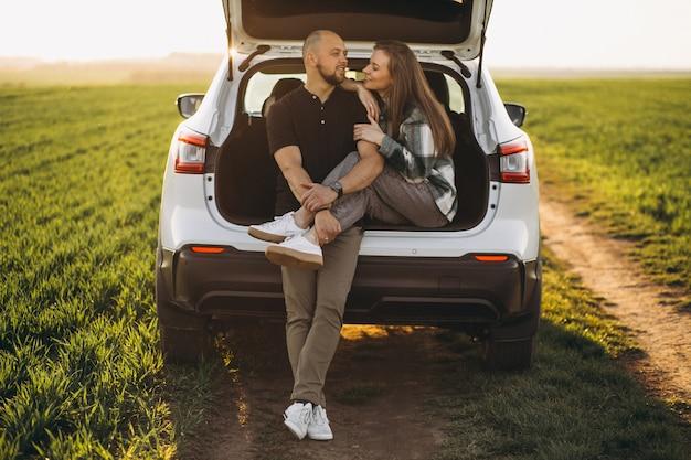 Casal sentado na parte de trás do carro no campo
