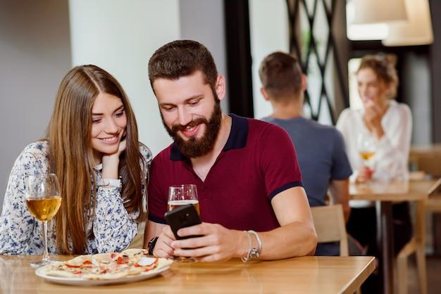 Casal sentado na pizzaria com pizza, vinho e cerveja.