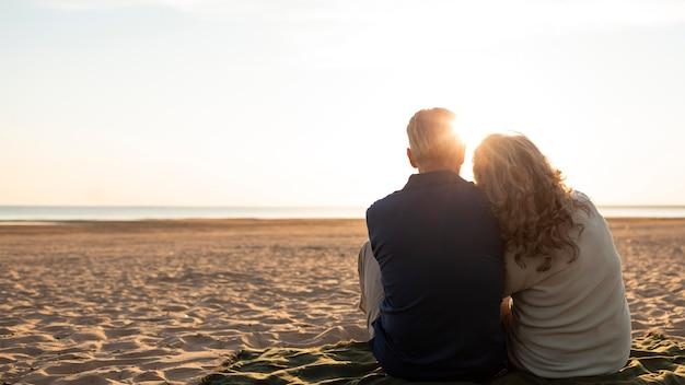 Casal sentado na praia, foto completa