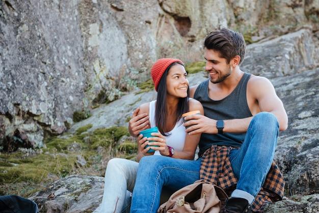 Casal sentado na rocha com xícaras de chá. olhos nos olhos