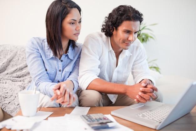 Casal sentado na sala de estar fazendo banca online