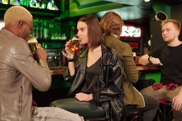 Casal sentado no balcão do bar bebendo cerveja junto com outras pessoas ao fundo