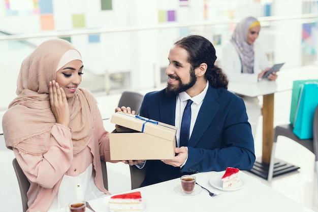 Casal sentado no café depois das compras. mulher em hijab.