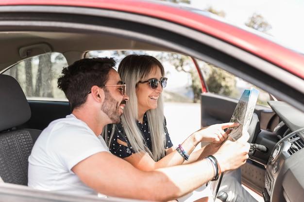 Casal sentado no carro à procura de direção no mapa