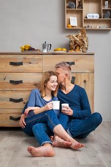 Casal sentado no chão, bebendo uma xícara de café
