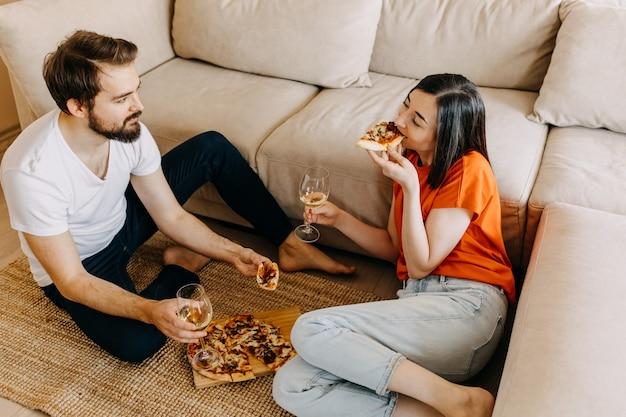 Casal sentado no chão, comendo pizza e bebendo vinho