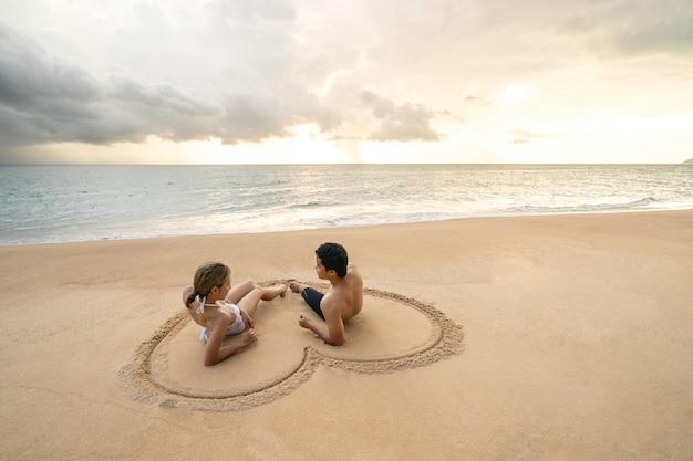 Casal sentado no coração, desenhando na praia de areia, relaxantes banhos de sol.