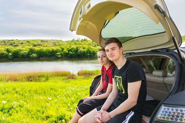 Casal sentado no para-choque traseiro do veículo suv estacionado em green field perto do rio em dia ensolarado e olhando para a câmera